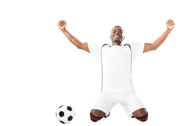 happy young triumphing african american soccer player kneeling near ball isolated on white   - Photo, Image