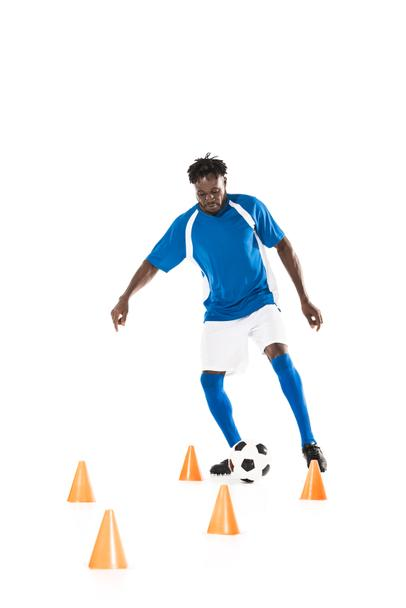 young african american sportsman training with soccer ball and marker cones isolated on white  - Photo, Image