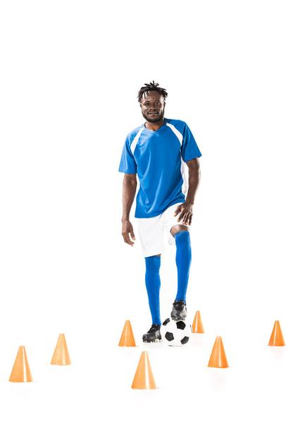 young african american sportsman standing with soccer ball between marker cones and smiling at camera isolated on white - Photo, Image