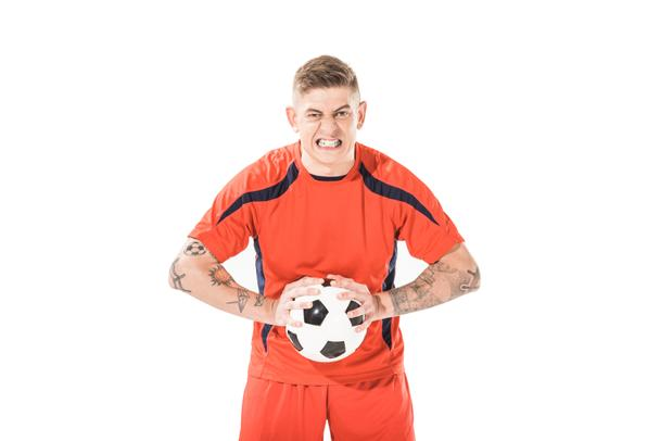 angry young soccer player holding ball and looking at camera isolated on white - Photo, Image