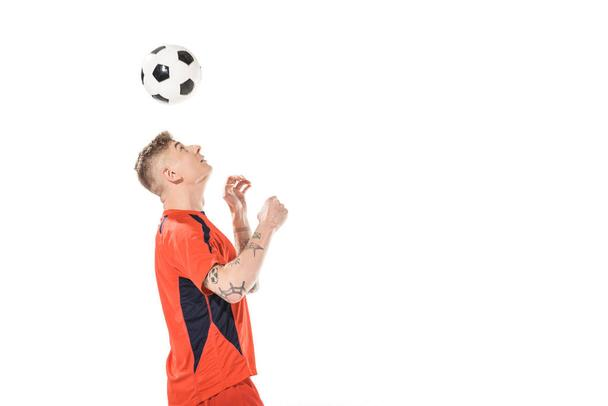 young soccer player hitting ball with head and looking up isolated on white  - Photo, Image