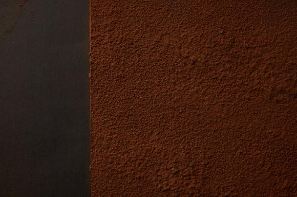 top view of delicious brown cocoa powder on black background  - Photo, Image