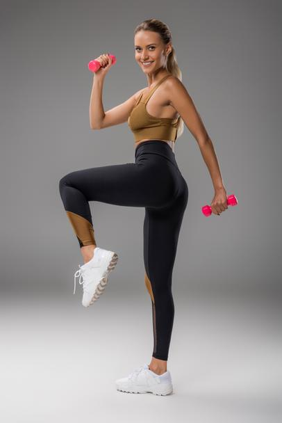 sportive young woman doing exercise with dumbbells on grey - Photo, Image