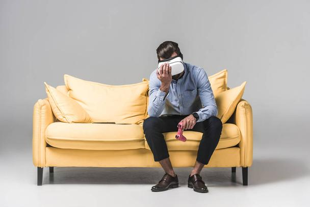 upset man lost in video game with joystick and virtual reality headset on yellow sofa on grey - Photo, Image