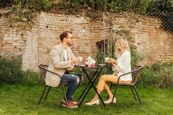 side view of couple sitting at table in cafe with cups of coffee and bouquet on table - Photo, Image
