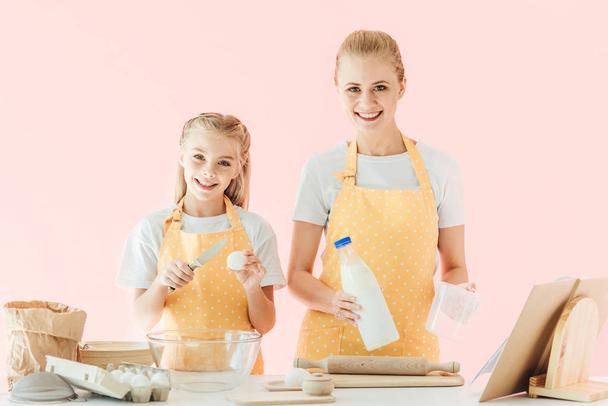 happy mother and daughter looking at camera while preparing dough isolated on pink - Photo, Image