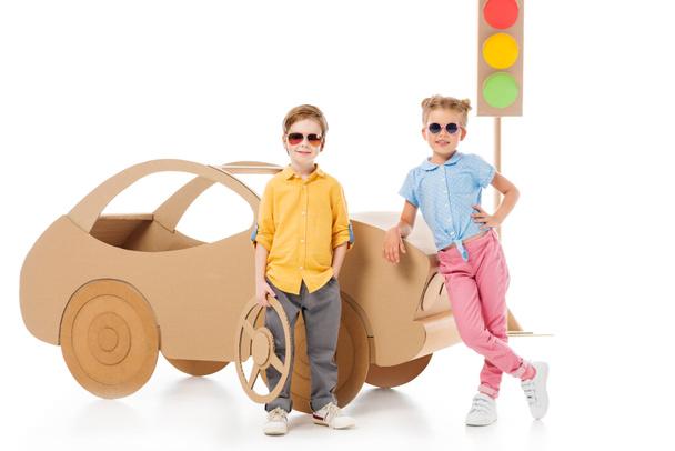 stylish children in sunglasses posing near cardboard car and traffic lights, on white  - Photo, Image