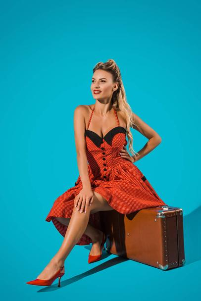 attractive young pin up woman in retro dress sitting on suitcase on blue backdrop - Photo, Image