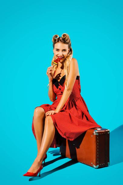 pretty pin up woman in retro style dress with lollipop sitting on suitcase on blue backdrop - Photo, Image