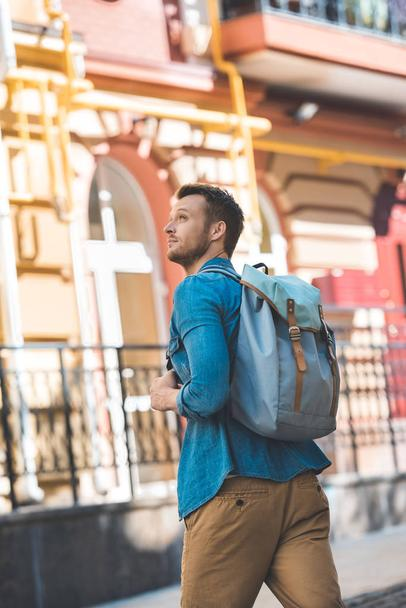 attractive young tourist with backpack walking by street and looking up - Photo, Image