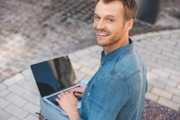 high angle view of handsome young man using laptop with blank screen on street and looking at camera - Photo, Image