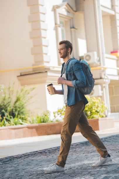 attractive young man with coffee to go and backpack walking by city - Photo, Image