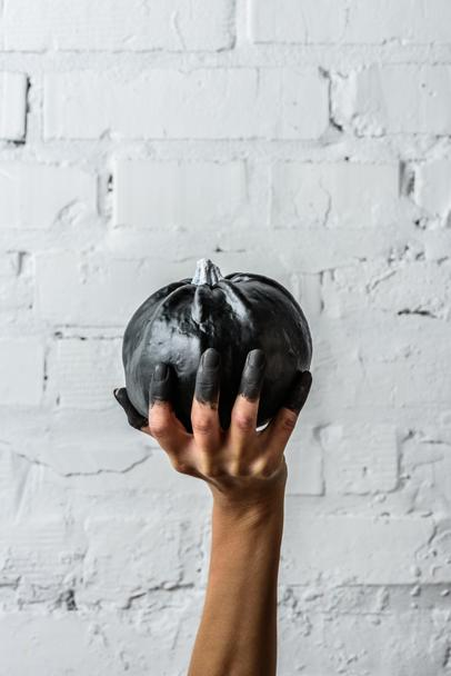 cropped shot of woman holding black painted halloween pumpkin in front of white brick wall - Photo, Image