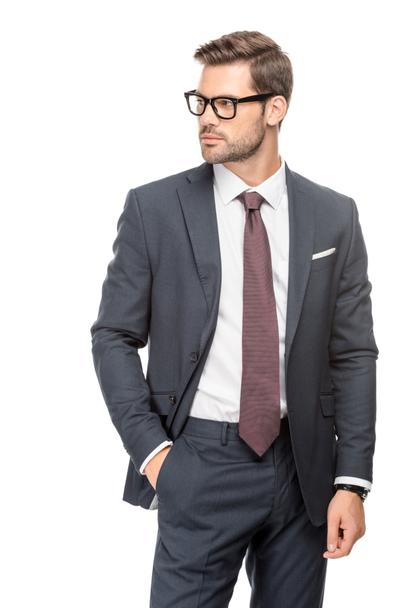 attractive young businessman in suit and eyeglasses and looking away isolated on white - Photo, Image