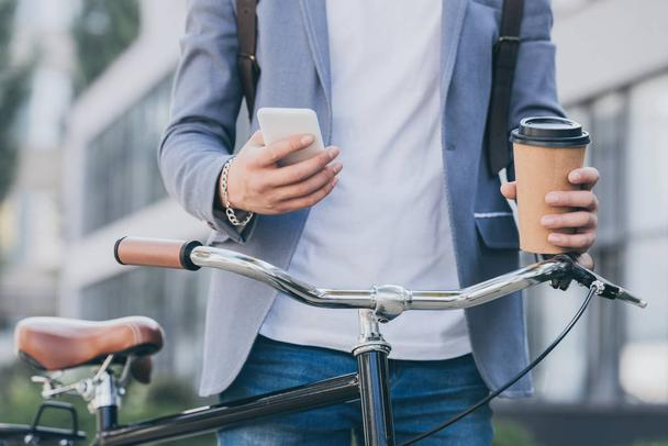 partial view of man holding disposable cup of coffee and using smartphone near bicycle - Photo, Image