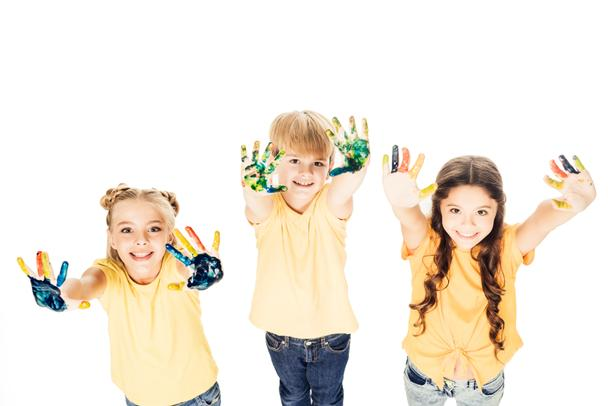 high angle view of happy kids showing hands in paint and smiling at camera isolated on white - Photo, Image