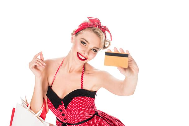 high angle view of cheerful woman in pin up clothing with shopping bags showing credit card isolated on white - Photo, Image