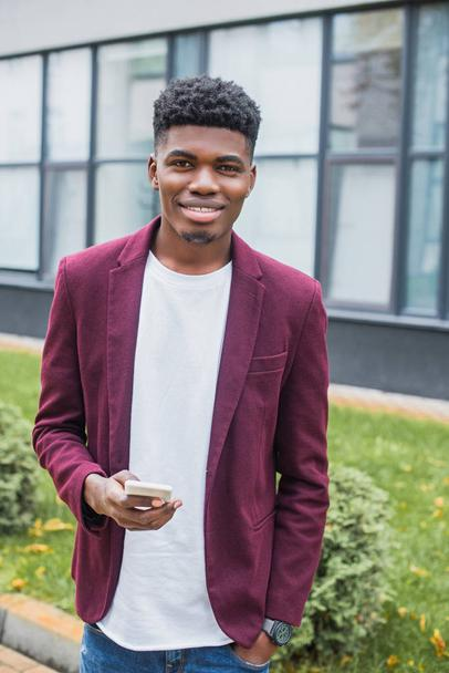 smiling young man with smartphone looking at camera on street - Photo, Image