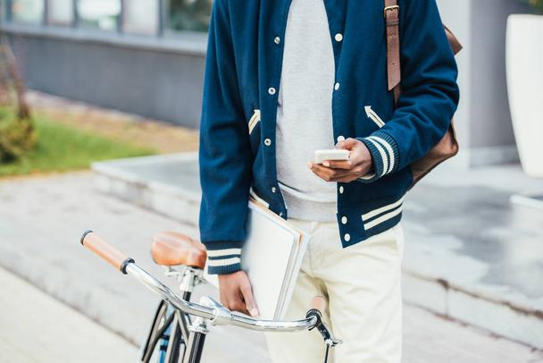 cropped view of stylish african american teleworker with documents using smartphone and standing near bike - Photo, Image