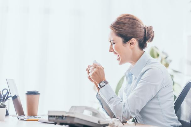 side view of mad adult businesswoman crumpling paper at workplace - Photo, Image