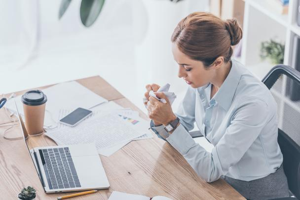 high angle view of stressed adult businesswoman crumpling paper at workplace - Photo, Image