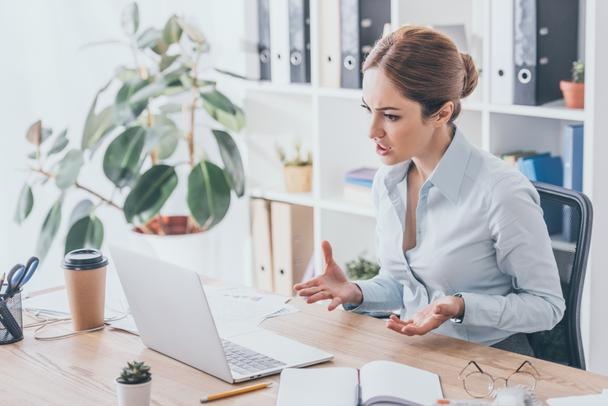 stressed adult businesswoman looking at laptop screen at office - Photo, Image