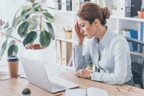 overworked adult businesswoman with headache sitting at workplace - Photo, Image