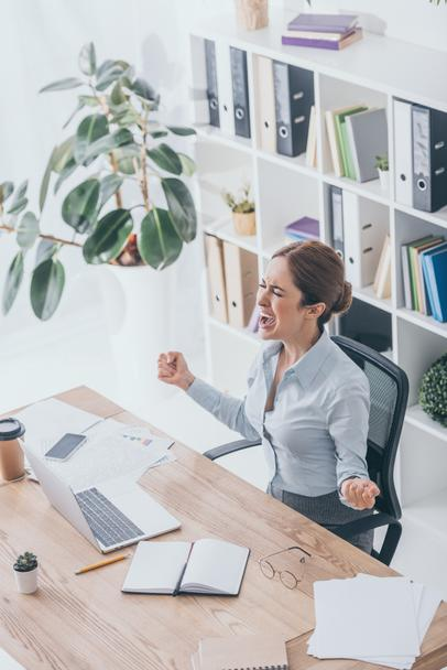 high angle view of stressed adult businesswoman screaming at workplace - Photo, Image