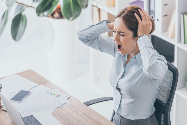 high angle view of stressed businesswoman holding her head and screaming at workplace - Photo, Image