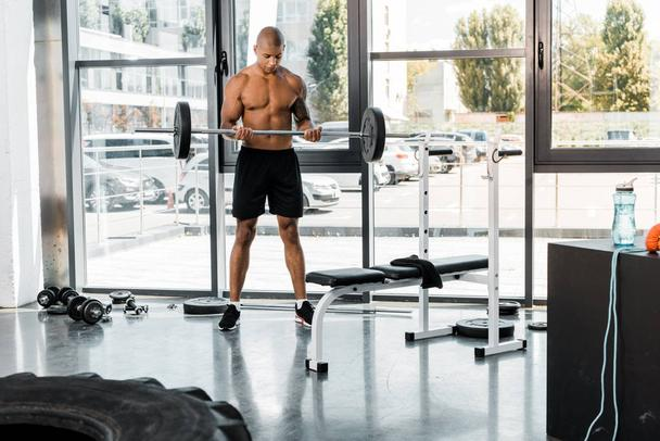 muscular shirtless african american man lifting barbell in gym - Photo, Image