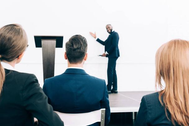 selective focus of smiling african american speaker pointing on screen in conference hall - Photo, Image
