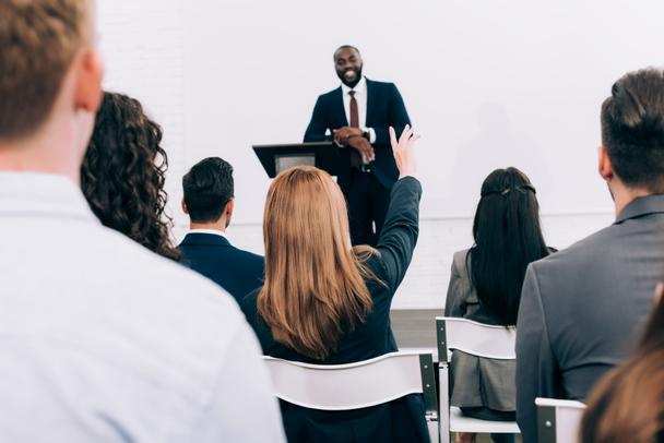 african american lecturer talking to audience during seminar in conference hall, participant raising hand - Photo, Image