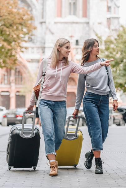 female tourists with backpacks and baggage walking on city street - Photo, Image