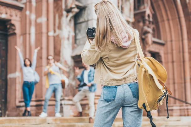 blonde woman taking photo of tourists on camera in city - Photo, Image