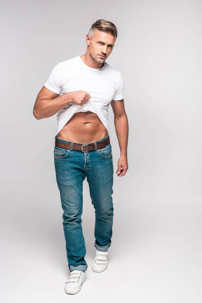 full length view of handsome man in white t-shirt and denim pants looking at camera on grey - Photo, Image