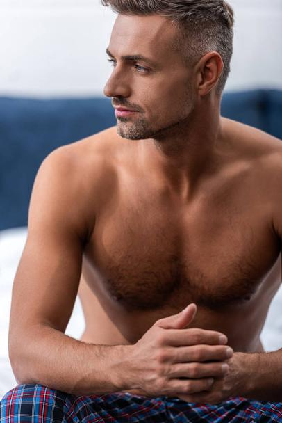 thoughtful shirtless man sitting on bed and looking away at home - Photo, Image
