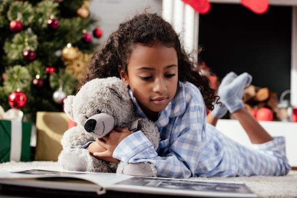 adorável criança afro-americana em pijama com ursinho de pelúcia olhando para álbum de fotos no chão em casa  - Foto, Imagem