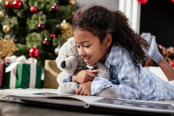 criança americana africana adorável feliz em pijama com ursinho de pelúcia olhando para álbum de fotos no chão em casa  - Foto, Imagem