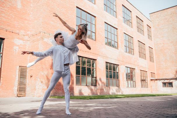 молодих артистів балету в білий одяг, танці на міських вулиць міста     - Фото, зображення