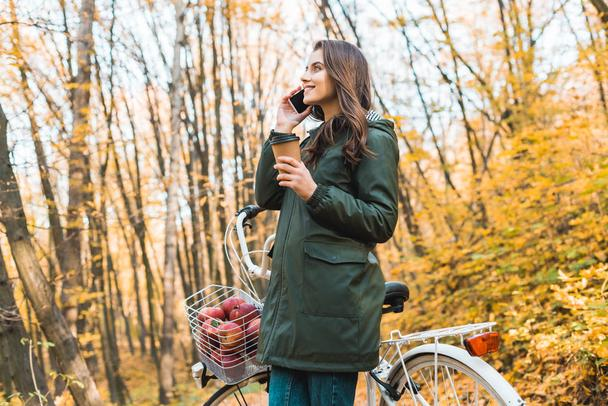 low angle view of happy woman with coffee cup talking on smartphone near bicycle in autumnal forest  - Photo, Image