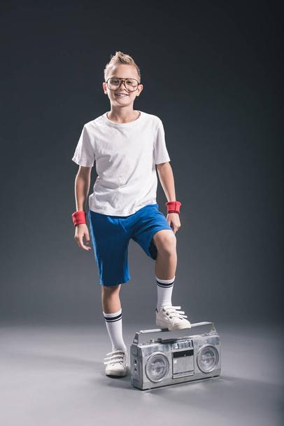 smiling preteen boy in eyeglasses with boombox posing on grey backdrop - Photo, Image