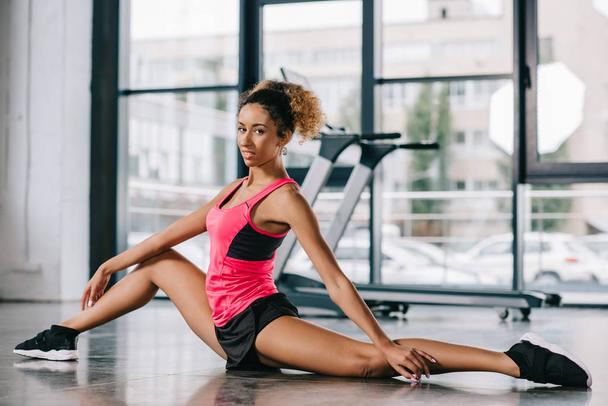 beautiful african american sportswoman stretching on floor at gym - Photo, Image