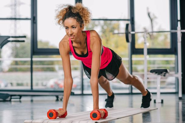 young african american sportswoman doing plank with dumbbells on fitness mat at gym - Photo, Image