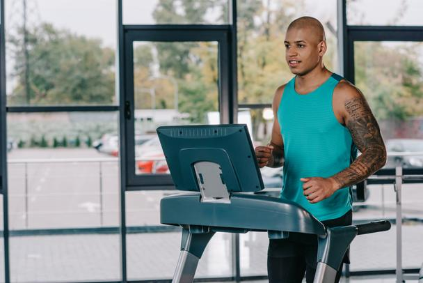young african american sportsman running on treadmill at gym - Photo, Image