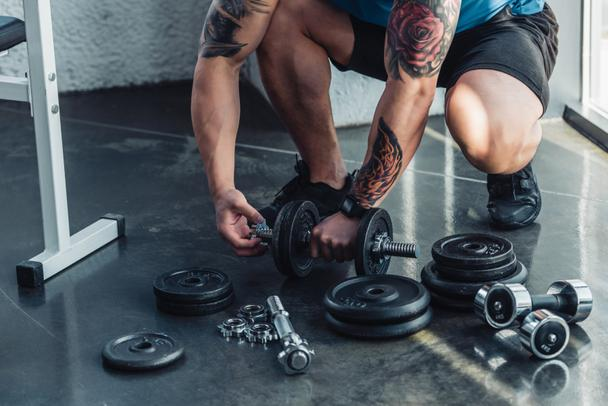 partial view of tattooed sportsman assembling dumbbells - Photo, Image