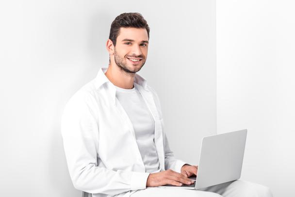adult smiling handsome man in total white using laptop - Photo, Image