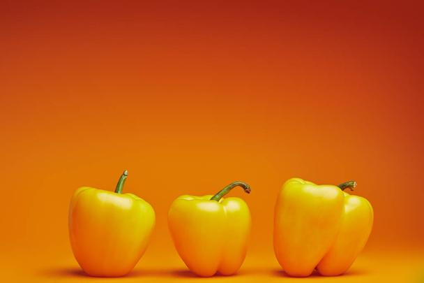 close-up view of fresh ripe bell peppers on orange background   - Photo, Image