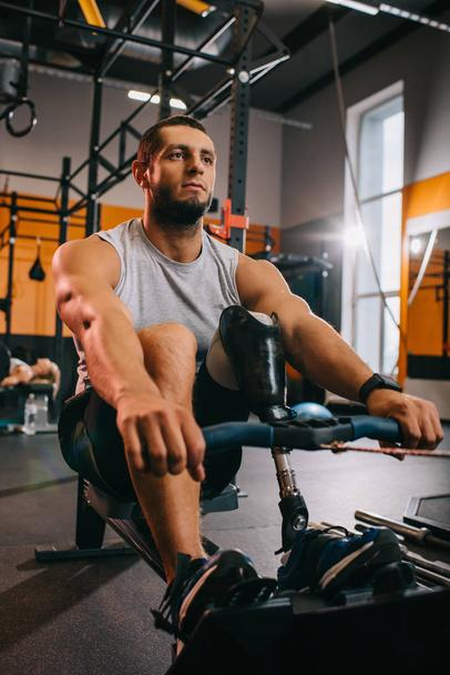 handsome young sportsman with artificial leg working out with rowing machine at gym - Photo, Image