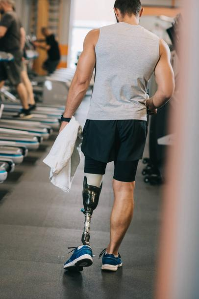 rear view of sportsman with artificial leg walking by gym - Photo, Image