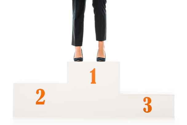 cropped view of businesswoman standing on winners podium isolated on white - Photo, Image